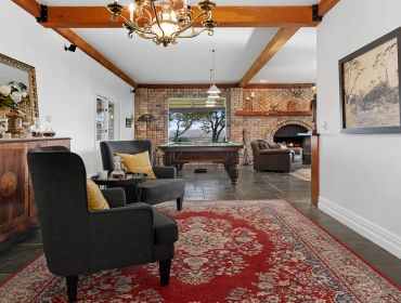 The Homestead Event and Wedding Venue, Eagle Ridge Country Estate, rustic lounge, black leather seats and red rug
